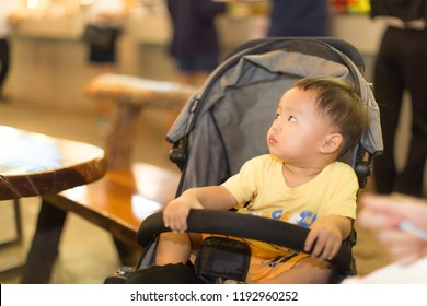 Zooming closeup view of a young lovely charming little Asian boy baby dresses in yellow clothes sitting on a black perambulator in an outdoor restaurant while glancing to the other side