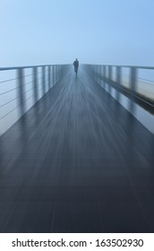 Zooming in (radial blur) on a man running into the fog on a modern footbridge.