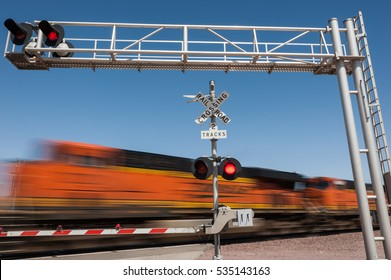Zooming train engine speeding past railroad crossing