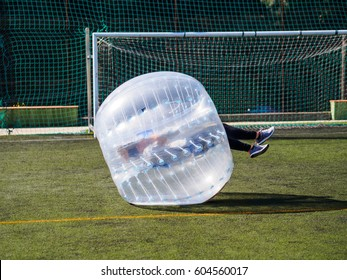 Zorb. Outdoor toys. Bubble football, soccer. Sport team, girl falling to the ground, overturning