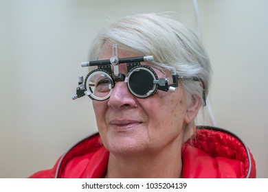 Zrenjanin, SERBIA, February 2018: Elderly woman wearing phoropter or trial frame and looking at mirrored eye test chart during sight test at optometric.