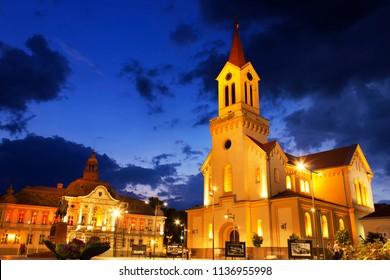 ZRENJANIN, SERBIA - JUNE 3, 2018: Town square at night. Municipality building and Catholic church in Zrenjanin.