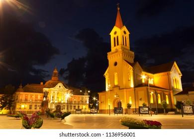 ZRENJANIN, SERBIA - JUNE 3, 2018: Town square at night. Municipality building and Catholic church