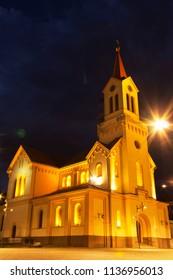 ZRENJANIN, SERBIA - JUNE 3, 2018: Town square at night. Catholic church in Zrenjanin