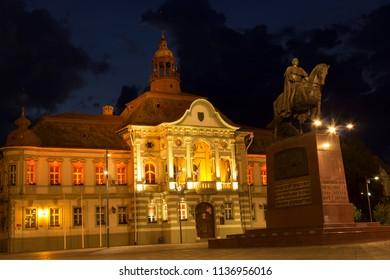 ZRENJANIN, SERBIA - JUNE 3, 2018: Town square at night. Municipality building and monument of King Petar I Karadjordjevic