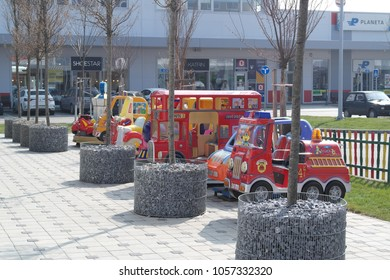 Zrenjanin, Serbia - March 28th, 2018: The row of coin-operated kids' rides (kiddie rides) behind the row of trees whose bottom part of trunk is decorated with little stones and circular wire