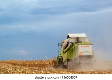 ZRENJANIN, SERBIA - SEPTEMBER 19, 2017: Claas combine harvester working on corn field. Lower maize crop yield expected this year in Vojvodina region due to drought during summer.