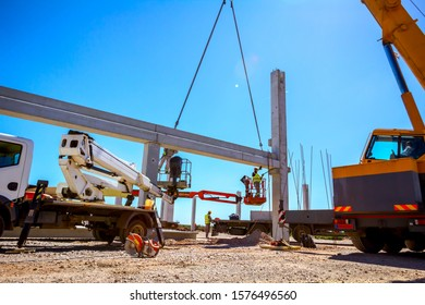 Zrenjanin, Vojvodina, Serbia - April 20, 2018: Worker is helping mobile crane to manage concrete joist for assembly huge construction.