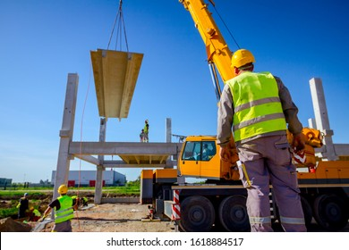 Zrenjanin, Vojvodina, Serbia - April 20, 2018: View from behind on construction worker with safety vest and yellow helmet overseeing mobile crane to manage concrete joist for assembly huge constructio