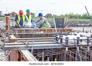 Zrenjanin, Vojvodina, Serbia - April 30, 2015: Industrial shot of construction worker who is welding metal frame, cage of armature inside of demountable wooden mold for concreting pillar base.