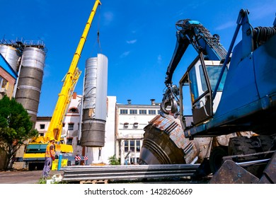 Zrenjanin, Vojvodina, Serbia - June 08, 2018: Loader machine with hydraulic grappling claw and crane are bringing down heavy metal silo in industrial complex.