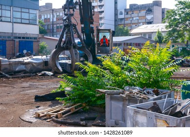 Zrenjanin, Vojvodina, Serbia - June 08, 2018: View on machine, loader manipulator with hydraulic grappling claw until is collecting, moving old steel, scrap metal.