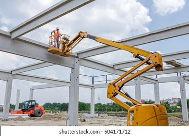 Zrenjanin, Vojvodina, Serbia - June 4, 2015: Worker is managing the orange cherry picker across building site.