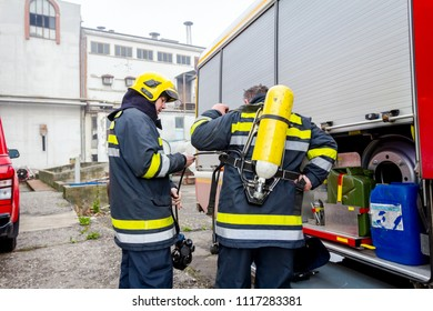 Zrenjanin, Vojvodina, Serbia - March 27, 2018: Firefighter is helping fellow to assembly his gear, keep balance and direction, checking equipment.