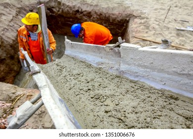 Zrenjanin, Vojvodina, Serbia - March 30, 2018: Workers are spreading fresh concrete in square trench pouring from mixer truck.