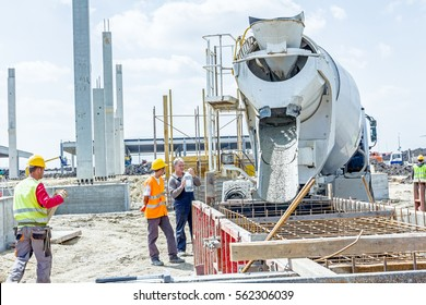 Zrenjanin, Vojvodina, Serbia - May 29, 2015: Workers at building site are pouring concrete in mold from mixer truck.