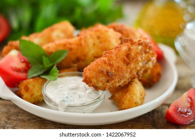 Zucchini in batter on a white plate, decorated with a sprig of greenery and slices of tomatoes