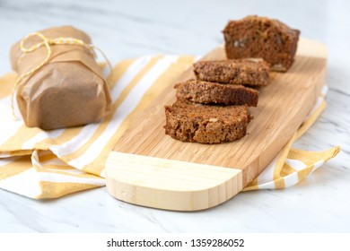 Zucchini Bread Sliced on Bamboo Cutting Board; Second Loaf Wrapped in Parchment Paper; Yellow and White Kitchen Towel; White Countertop