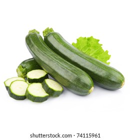 zucchini courgette decorated with green leaf lettuce. Isolated on white