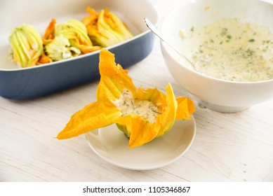 zucchini  or courgette flowers are filled with ricotta cream, preparing a mediterranean appetizer on a white wooden table, selected focus, narrow depth of field