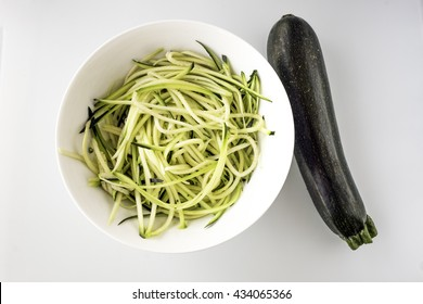 Zucchini (courgette) in white bowl lay flat on white chopping board background