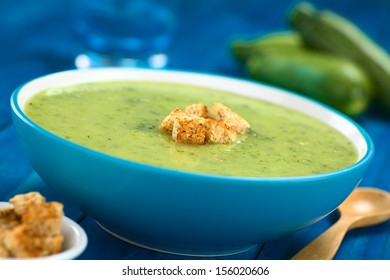 Zucchini cream soup with wholewheat croutons served in blue bowl with wooden spoon on the side, zucchini and glass in the back (Selective Focus, Focus on the front of the croutons)