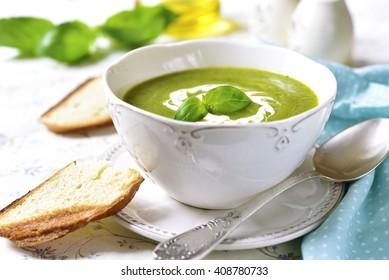 Zucchini creamy soup with basil on a light background.