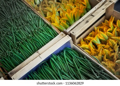 Zucchini flowers and green beans on a market stall in Summer