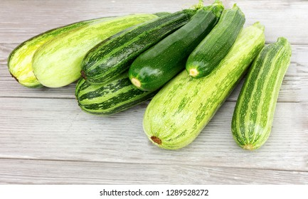 Zucchini. Fresh zucchini or courgette on wooden background. Heap of green vegetable marrow.