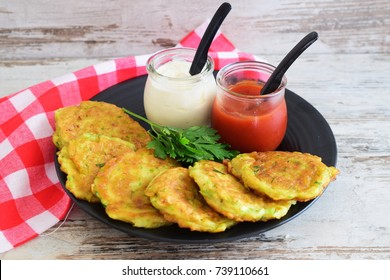 Zucchini fritters on a black plate with tomato sauce and Greek yogurt in glass jars on a wooden background. Healthy eating concept.