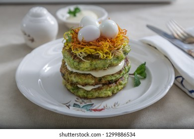 Zucchini fritters, vegetarian zucchini pancakes, served with quail eggs and carrots on top
