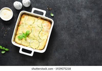 Gâteau de courgette avec sauce au bechamel et parmesan sur fond béton foncé. Tarte d'été aux courgettes.