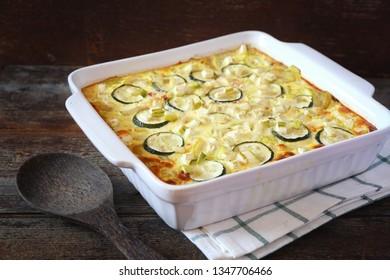 Zucchini gratin in ceramic dish on wooden background