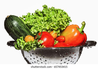 Zucchini, lettuce, bell pepper and tomatoes in a colander.
