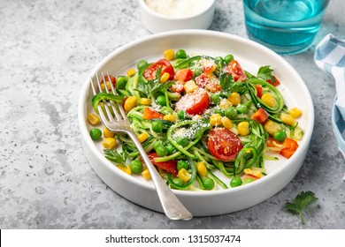 zucchini noodle with tomato, corn and green peas on white plate, healthy vegan food, selective focus