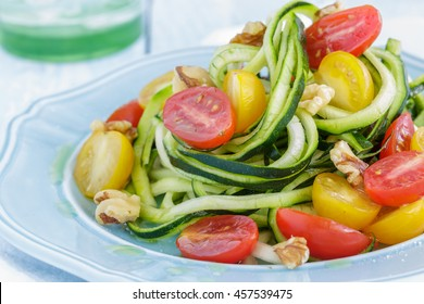 Zucchini noodles with tomatoes and walnuts tossed in olive oil