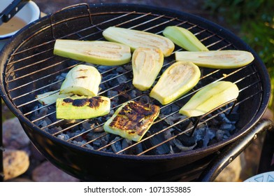 Zucchini on the grill over the coals in a round grill
