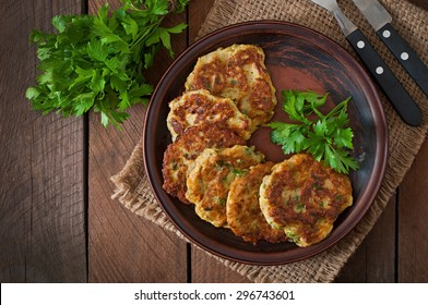 Zucchini pancakes with parsley on a wooden table. Top view