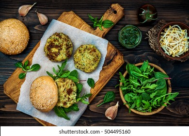 Zucchini quinoa veggie burger with pesto sauce and sprouts. Vegetarian burger on a cooking sheet ready to prepare hamburger. Top view, overhead, flat lay