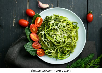 Zucchini raw vegan pasta with avocado dip sauce, spinach leaves and cherry tomatoes on plate. On dark background. Vegetarian healthy food