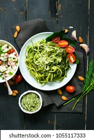Zucchini raw vegan pasta with avocado dip suace, spinach leaves and cherry tomatoes on plate. On dark background. Vegetarian healthy food
