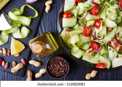 zucchini ribbon salad with tomatoes, roasted peanuts, red onion and greens on a black plate on a wooden table with ingredients on slate plate, italian cuisine, view from above, close-up, flat lay