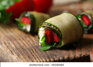 Zucchini rolls with cheese, bell peppers and arugula, close-up