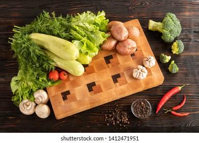 zucchini, salat, parsley, mushrooms, potatoes, tomato, garlic, broccoli, pepper spice and chili pepper on wooden background