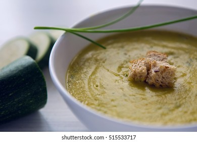 zucchini soup on a white wooden table with croutons in a bowl and sour cream in a Cup