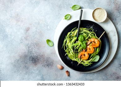 Zucchini spaghetti with pesto sauce and grilled shrimp skewers. Vegetarian vegetable low carb pasta. Zucchini noodles or zoodles.
