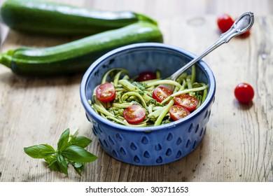 Zucchini spaghetti with rough basil and walnut pesto and cherry tomatoes