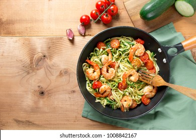 Zucchini spaghetti sauteed with tomato cherry and prawns in a pan on a rustic wooden table. Top view