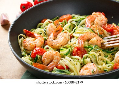 Zucchini spaghetti sauteed with tomato cherry and prawns in a pan on a rustic wooden table. Close up