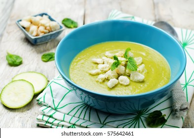 zucchini spinach soup on white wood background. toning. selective focus